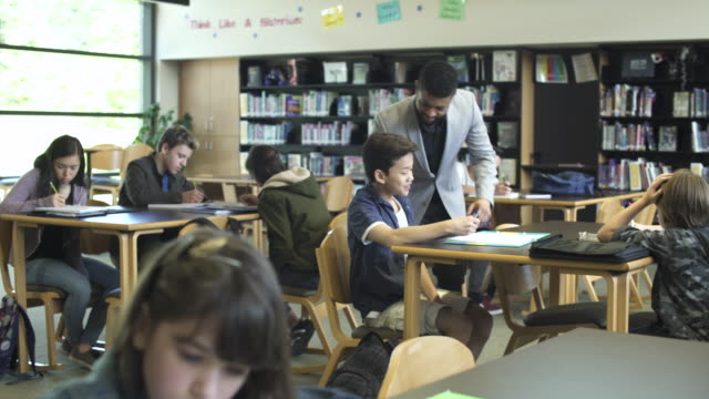 wide shot of teacher in high school library helping pupil - junior high stock videos & royalty-free footage