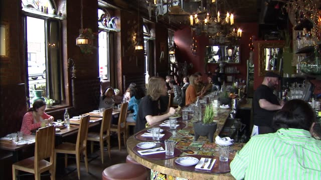 wide shot of the bar and tables at a mexican restaurant in brooklyn as patrons eat and drink, a medium shot of a young white couple looking at menus... - mexican restaurant stock videos & royalty-free footage
