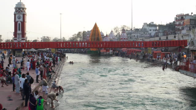 Wide shot of the bathing ghats on Ganges' banks wth pilgrims at Har ki Pauri in Haridwar, India