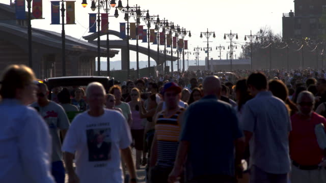 wide shot of the boardwalk at coney island.  the boardwalk is crowded with beachgoers and people taking the day at the beach. - coney island stock videos & royalty-free footage