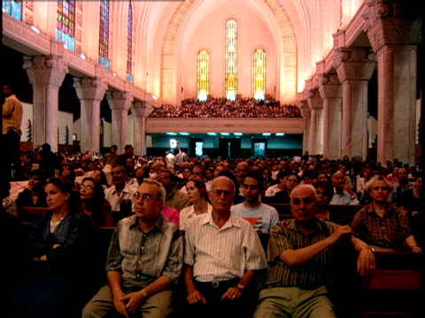 wide shot of the congregation in st. mark's cathredal in the abbassia district of cairo. they are listening to pope shenouda iii preaching. - congregation stock videos & royalty-free footage