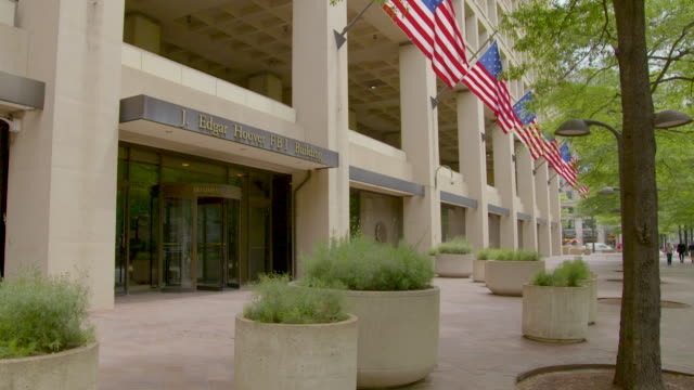wide shot of the entrance of the j. edgar hoover fbi building - fbi stock videos & royalty-free footage