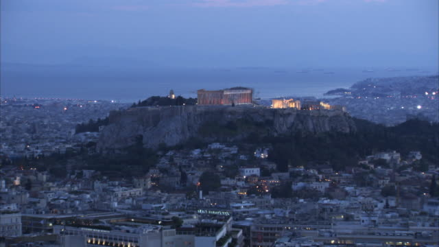 wide shot of the illuminated acropolis of athens at twilight, greece. - parthenon athens stock videos and b-roll footage