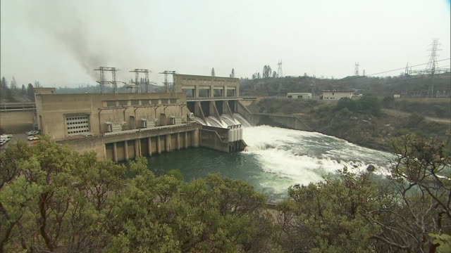 wide shot of the keswick dam with smoke from the nearby carr wildfires in the background on july 27, 2018 in redding, california. - environment or natural disaster or climate change or earthquake or hurricane or extreme weather or oil spill or volcano or tornado or flooding stock videos & royalty-free footage