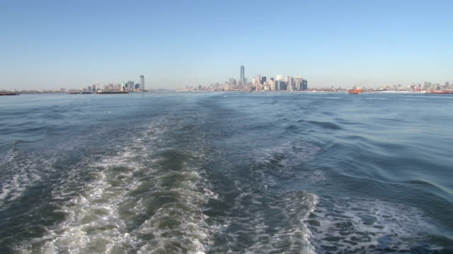 Wide shot of the Lower Manhattan Skyline in the distance as a ship sails towards the south in New York Harbor NO