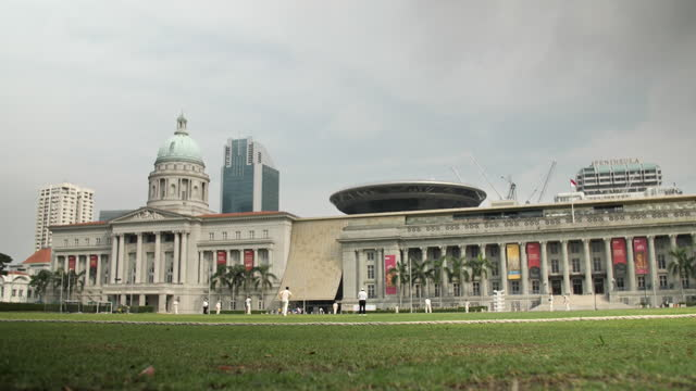 wide shot of the national gallery from the padang in singapore. people are playing cricket in the foreground. - クリケット選手点の映像素材/bロール