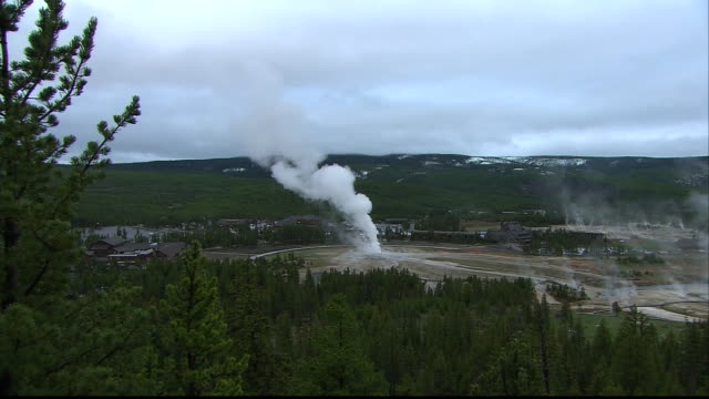 wide shot of the old faithful geyser at yellowstone national park in wyoming. - yellowstone national park stock videos & royalty-free footage