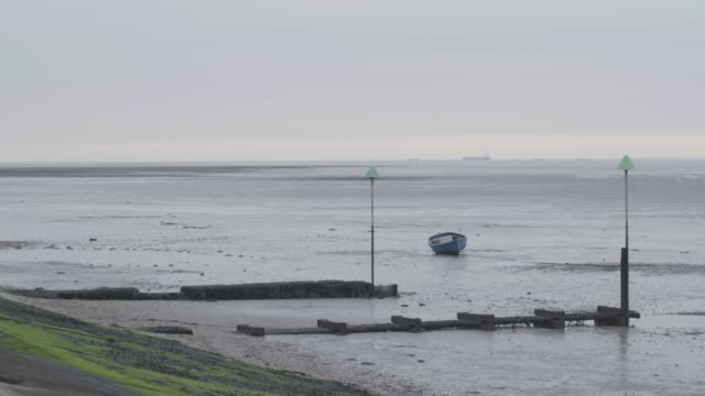 wide shot of the open sea at low tide with a fishing boat in the foreground - エセックス州点の映像素材/bロール