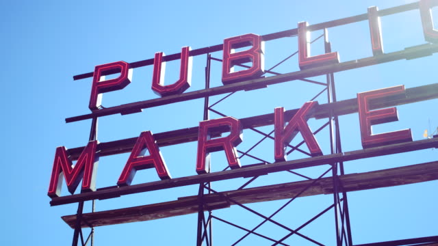vídeos de stock, filmes e b-roll de wide shot of the 'public market' sign at the iconic pike place market in downtown seattle washington no - pike place market