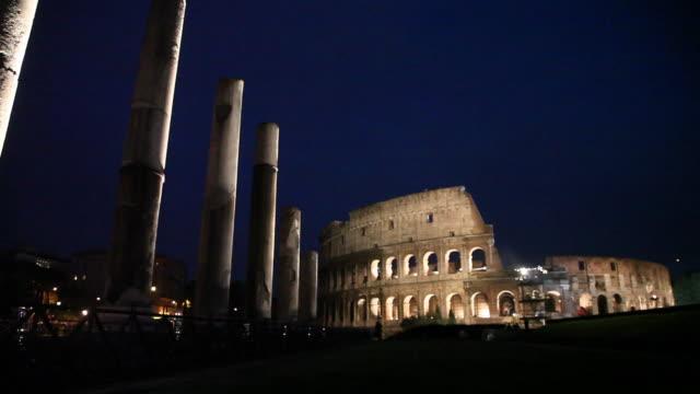 wide shot of the roman forum and ancient colosseum lit at night - geschichtlich stock-videos und b-roll-filmmaterial