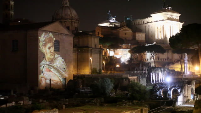 Wide shot of the Roman Forum lit at night