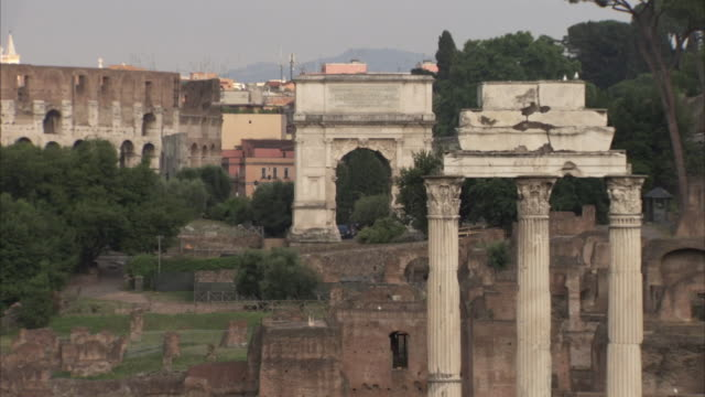 wide shot of the ruins of the temple of castor and pollux and the arch of titus at the forum in rome, italy. - ca. 7 jahrhundert stock-videos und b-roll-filmmaterial