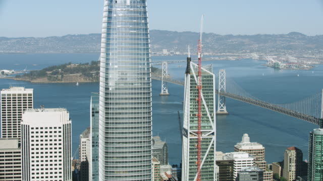 wide shot of the san francisco-oakland bay bridge with high-rise buildings in the foreground - san francisco bay stock videos & royalty-free footage