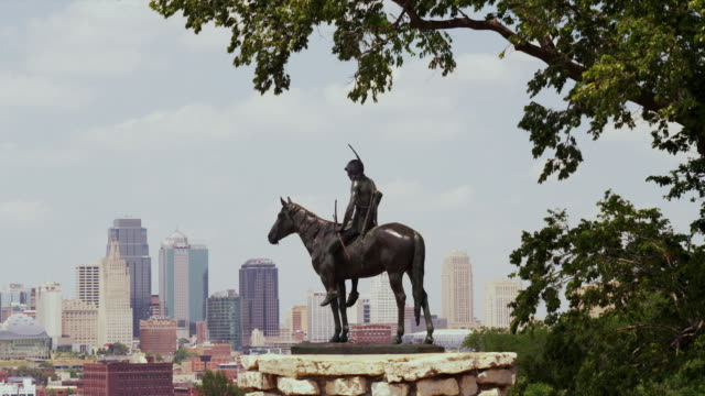 """wide shot of """"the scout,"""" a native american indian on a horse bronze statue by cyrus e dallin overlooking sky line of kansas city - statue stock videos & royalty-free footage"""