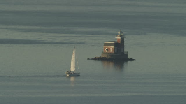wide shot of the stepping stone lighthouse with a sailboat - stepping stone stock videos & royalty-free footage
