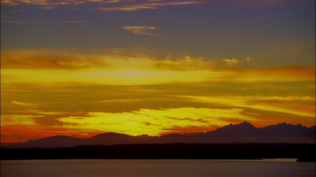 wide shot of the sun setting behind the mountains and over puget sound / seattle, washington - puget sound stock videos & royalty-free footage
