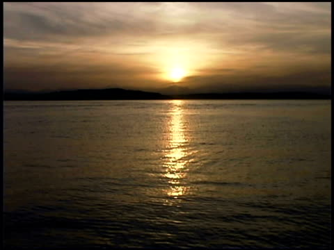 wide shot of the sun setting over the mountains surrounding the puget sound. - nordpazifik stock-videos und b-roll-filmmaterial