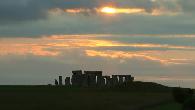 wide shot of the sun setting though the clouds at stonehenge on august 28, 2018 in wiltshire, england. - music or celebrities or fashion or film industry or film premiere or youth culture or novelty item or vacations stock videos & royalty-free footage