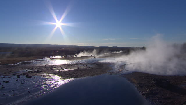 Wide shot of the sun shining over steam rising from a geothermal field in Iceland.