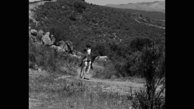 stockvideo's en b-roll-footage met wide shot of thief firing gun while riding horse on dirt track - alleen één mid volwassen man