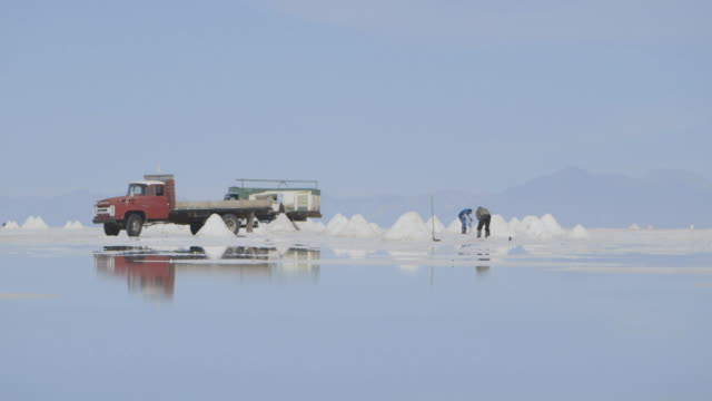 stockvideo's en b-roll-footage met wide shot of three men digging on the reflective salt plains of bolivia. - bolivia