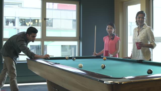 wide shot of three people playing billiards - キュー点の映像素材/bロール