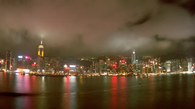 wide shot of time lapse clouds over hong kong skyline and harbor at night / central district - cinematography stock videos & royalty-free footage