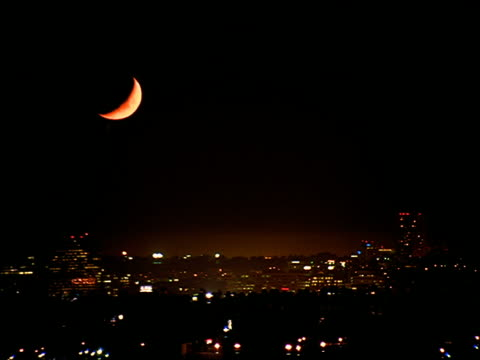 wide shot of time lapse moon setting over city