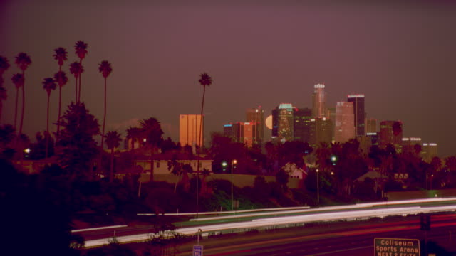 wide shot of time lapse moonrise over los angeles skyline /traffic in foreground - lockdown stock videos & royalty-free footage