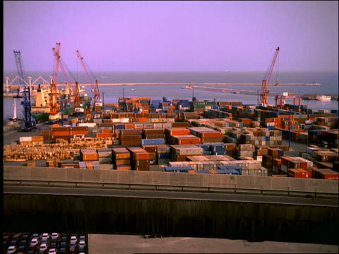 wide shot of time lapse shipping port with containers and freighters / Italy