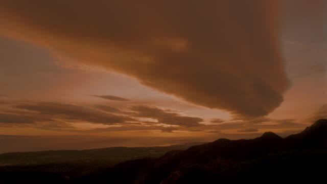 vídeos de stock, filmes e b-roll de wide shot of time lapse sunset + clouds over mountainous landscape - céu romântico