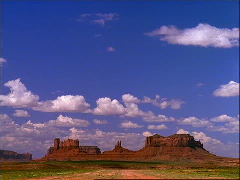 wide shot of time lapse white clouds in blue sky over monument valley - naturwunder stock-videos und b-roll-filmmaterial