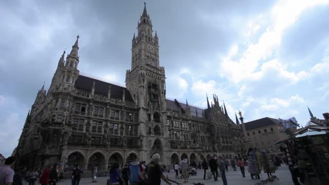 Wide shot of tourists around Munich, Marienplatz, New Town Hall.