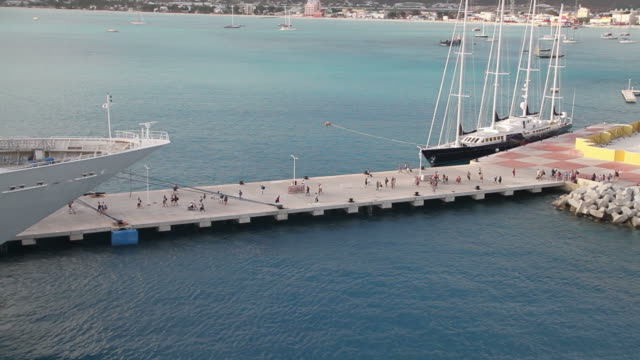 Wide shot of tourists getting on a cruise ship in Saint Marteen