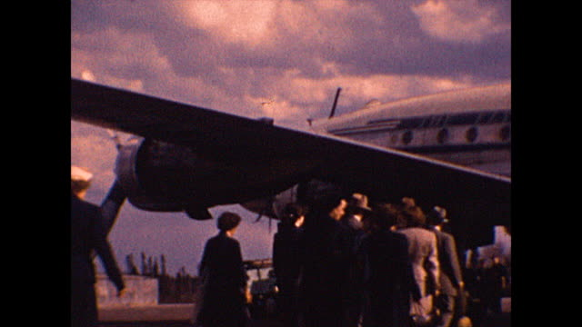 """wide shot of tourists in england are on the runway and boarding a plane named the """"flying dutchman"""" in england in 1952. from the collection of... - colour image stock videos & royalty-free footage"""