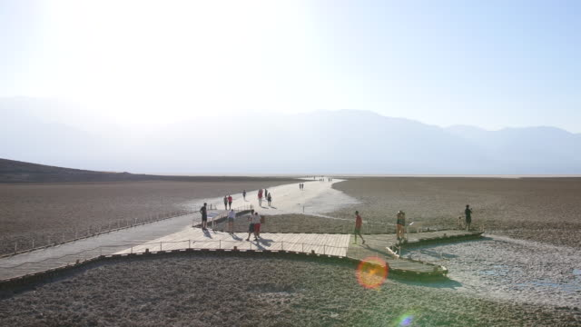 wide shot of tourists walking in the desolate landscape of badwater basin in death valley national park california - death valley national park stock videos & royalty-free footage