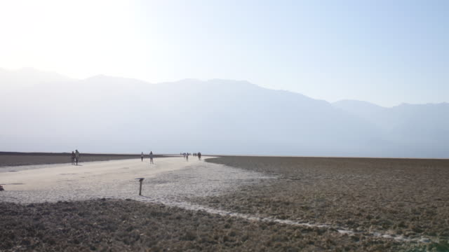 wide shot of tourists walking in the desolate landscape of badwater basin in death valley national park, california - death valley national park stock videos & royalty-free footage