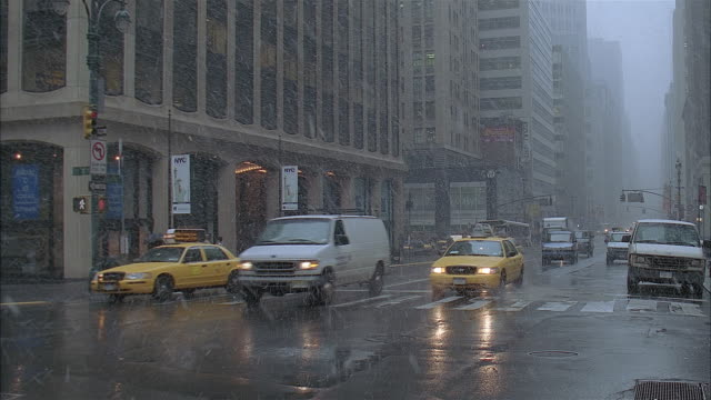wide shot of traffic driving down street and pedestrians walking on snowy day / bus pulling up to stop / new york city - banner stock videos & royalty-free footage