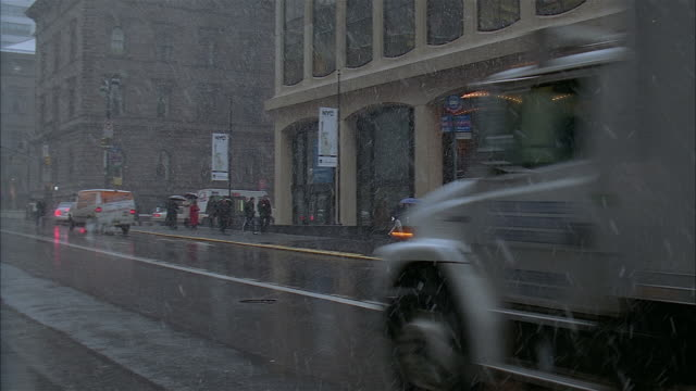 wide shot of traffic driving down street and pedestrians walking on sidewalk on snowy day / new york city - banner stock videos & royalty-free footage