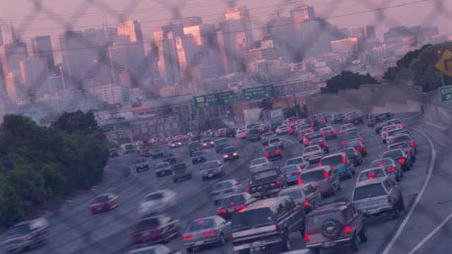 wide shot of traffic on highway with san francisco skyline in background - san francisco california stock videos & royalty-free footage