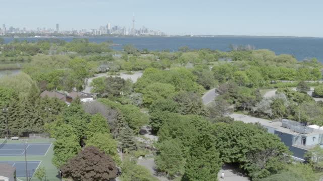 stockvideo's en b-roll-footage met wide shot of trees with city in background, toronto, ontario, canada. - ontariomeer