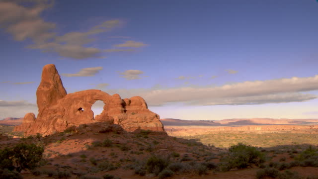 Wide shot of Turret Arch and desert landscape with bright blue skies and interesting clouds