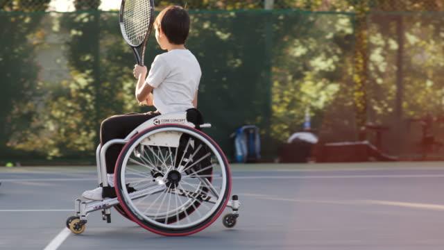 ダブルスをプレーする2人のアダプティブテニス選手のslo moワイドショット - テニス点の映像素材/bロール