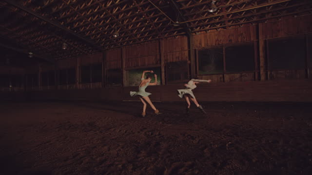 wide shot of two dancers dancing in wooden barn - pirouette stock videos and b-roll footage