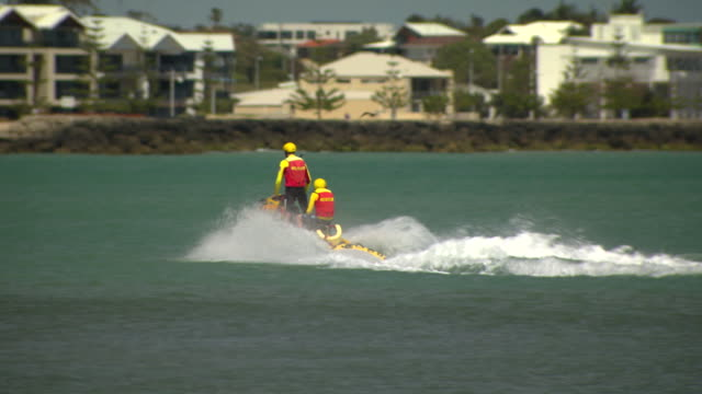 wide shot of two life savers riding jet ski waterfront apartments in the background / various shots of a covered speed boat on the water / wide shot... - bagnino video stock e b–roll