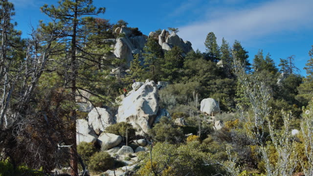 wide shot of two men climbing a boulder - granite rock stock videos and b-roll footage
