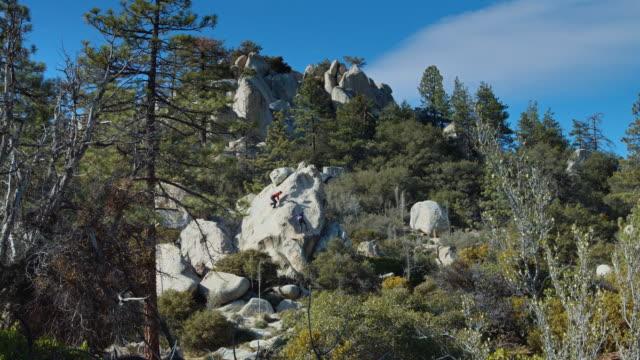 Wide Shot of Two Men Climbing a Boulder