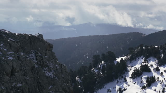wide shot of two men walking on a mountain ridge in a snowy valley in eastern anatolia. - anatolia stock videos and b-roll footage
