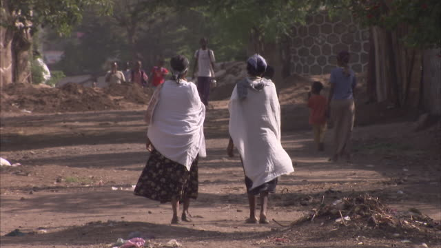 wide shot of two shawled women walking along a dusty road away from the camera - ethiopia stock videos & royalty-free footage