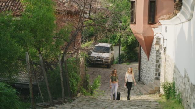 vídeos y material grabado en eventos de stock de wide shot of two women pulling suitcase uphill / plovdiv, bulgaria - sin mangas